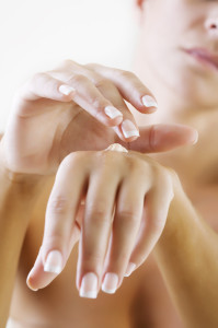 applying hand lotion to dry skin