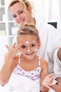 Mother and daughter applying face cream