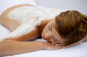 Young woman laid with cream on her back